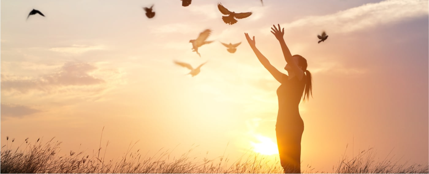 Woman letting go of a flock of birds during sunset