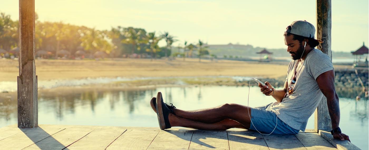 Man sits on lake dock reading smart phone