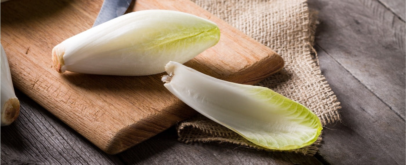Sliced pieces of endive on a wooden cutting board
