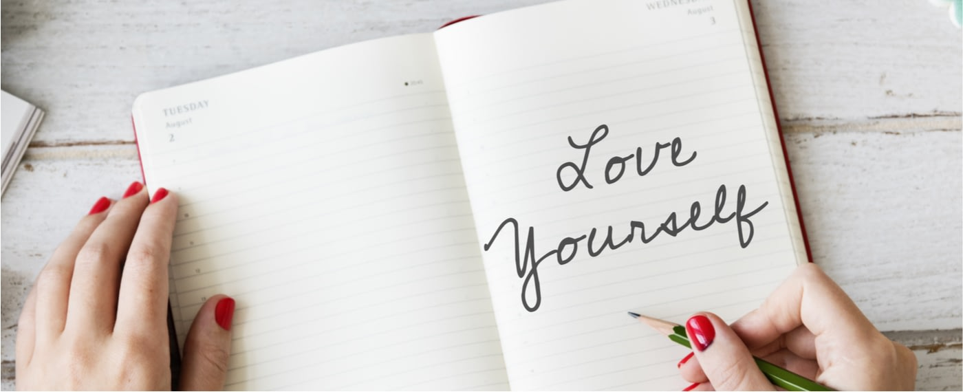 "A woman writes ""love yourself"" in her self-care journal"