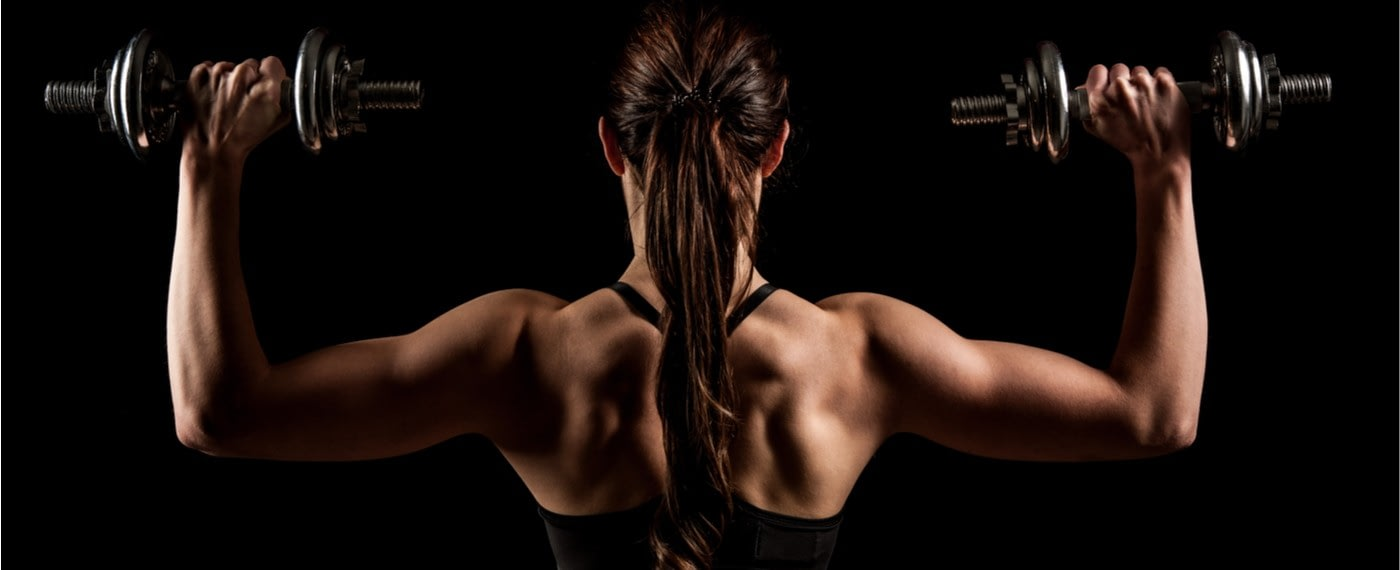 Athletic female showing off back muscles holding two dumbbells