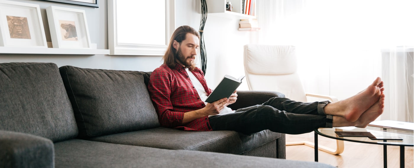 A man sits reading a book on men's health