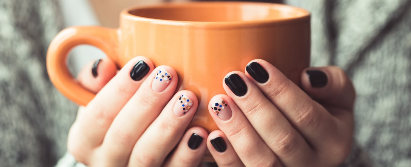 Trendy manicured nails holding a coffee mug
