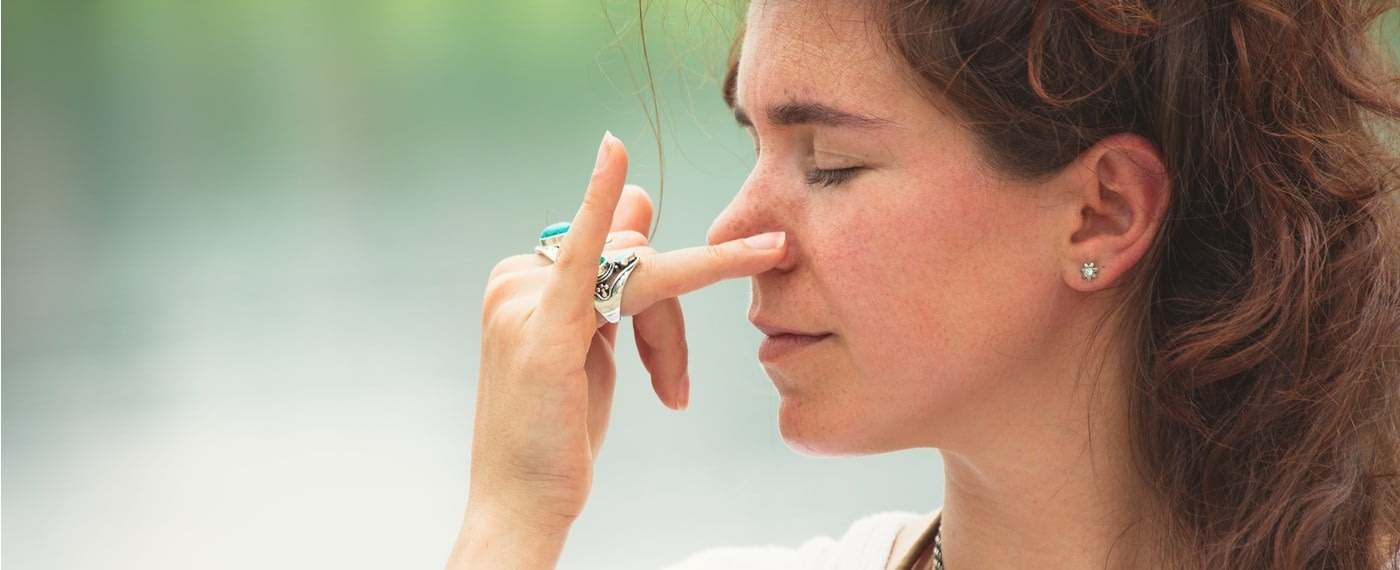 woman closing eyes and breathing out one nostril
