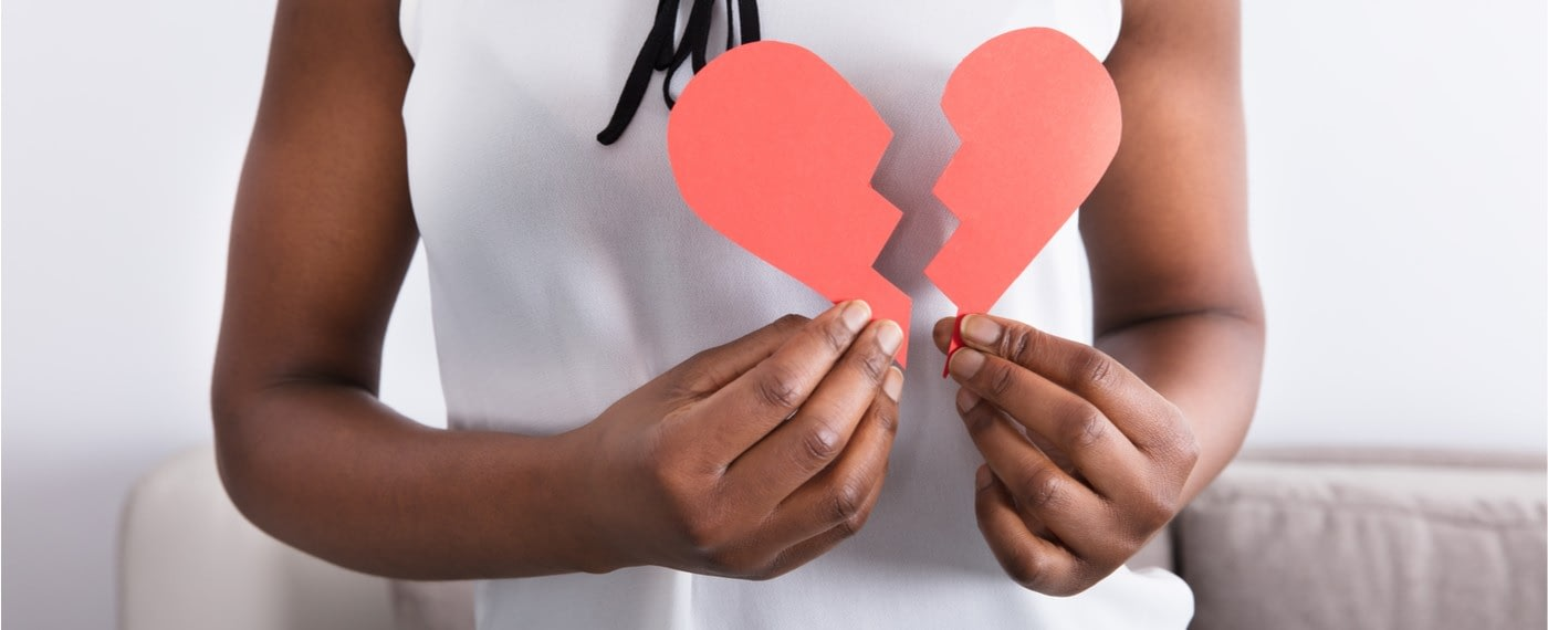 A young female holding a broken heart made of paper