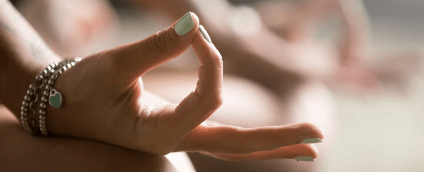 A woman with stylish nails meditates in a yoga pose