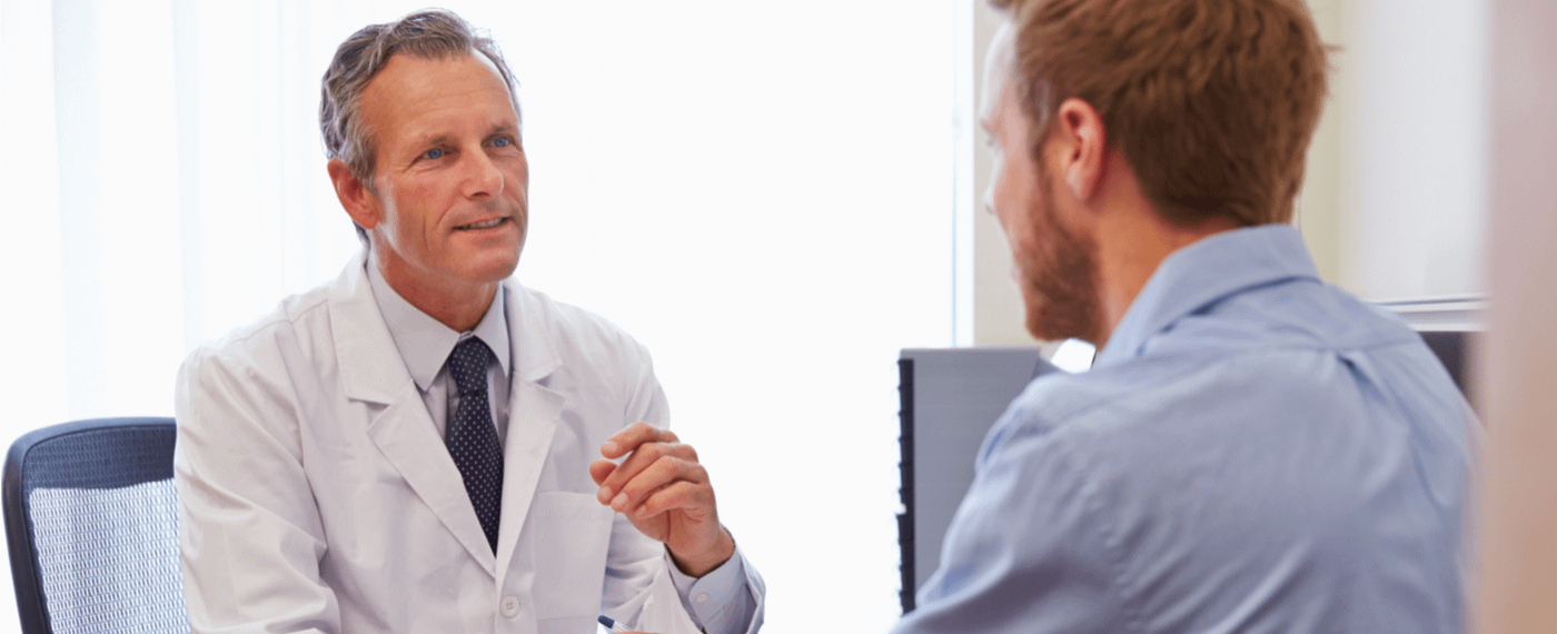 Male doctor sitting down speaking with male patient