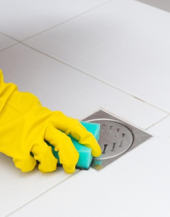 person scrubbing shower drain with a sponge
