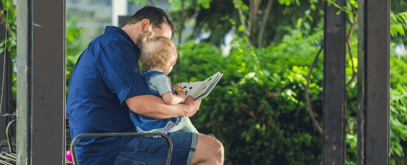 Father reading with young daughter