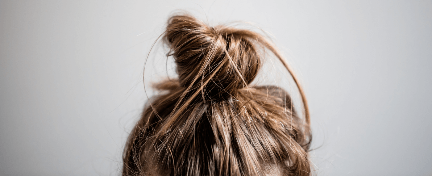 Messy blonde bun on top of woman's head