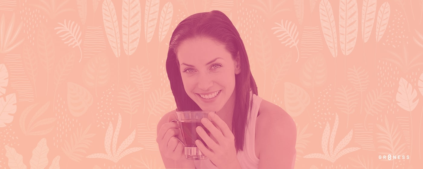 Woman smiles with a cup of tea in her hands