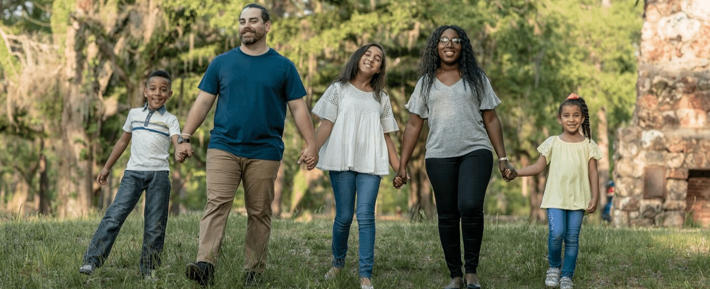 Family of five walking outside holding hands