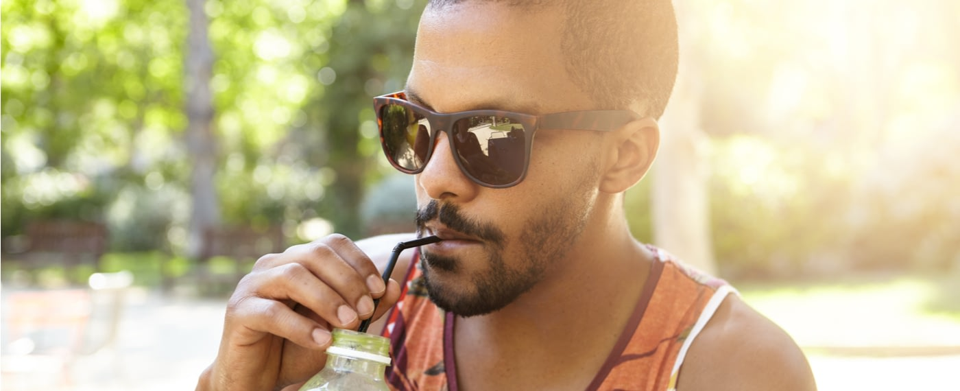 Man sipping from bottle with a straw