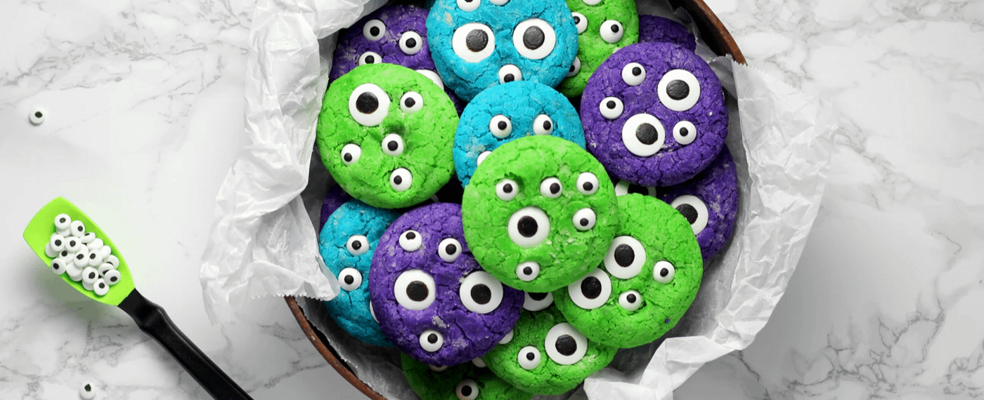 spooky halloween cookies in blue, green, and purple with googly eyes
