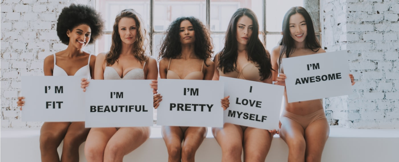 Five women holding up signs with positive self image quotes
