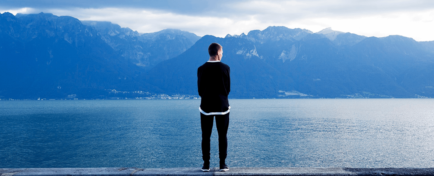 Man looking out over lake and mountains
