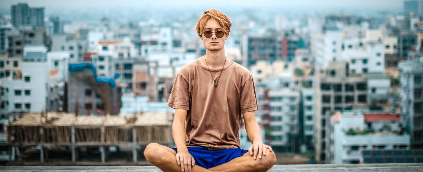 Man wearing sunglasses sitting cross legged