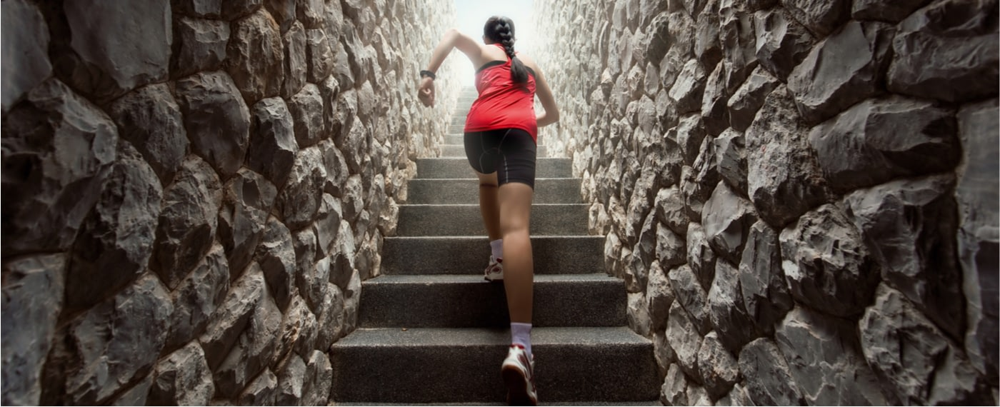 Woman in workout clothes running up stone steps