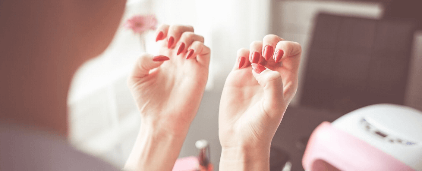 Woman's hands with long red fingernails