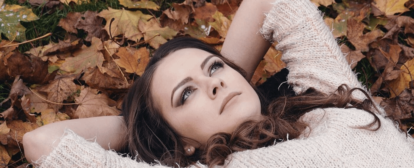 Dark haired woman laying in a pile of leaves