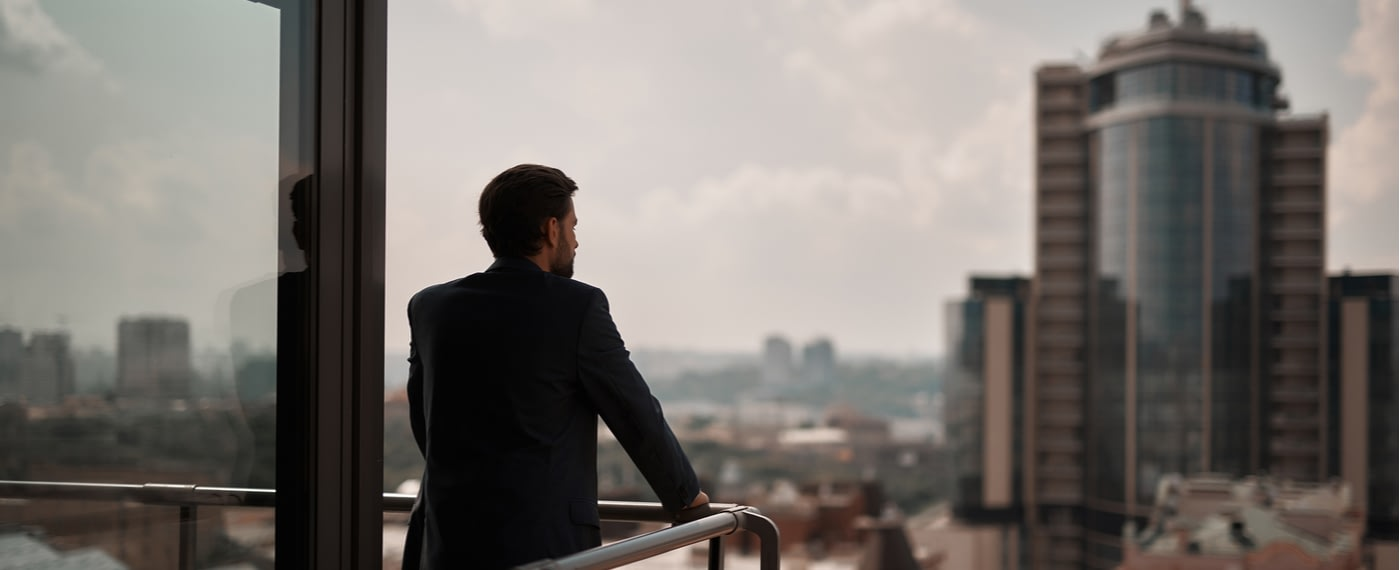 Man in a suit standing on balcony overlooking a city