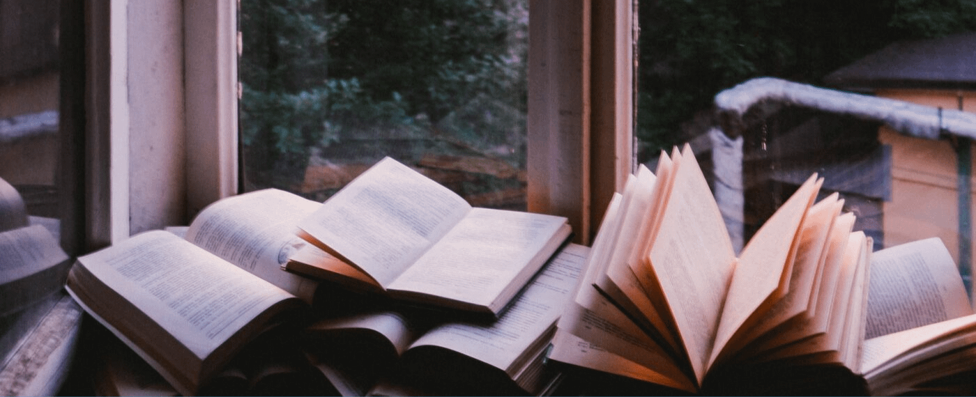 Pile of many open books next to a window