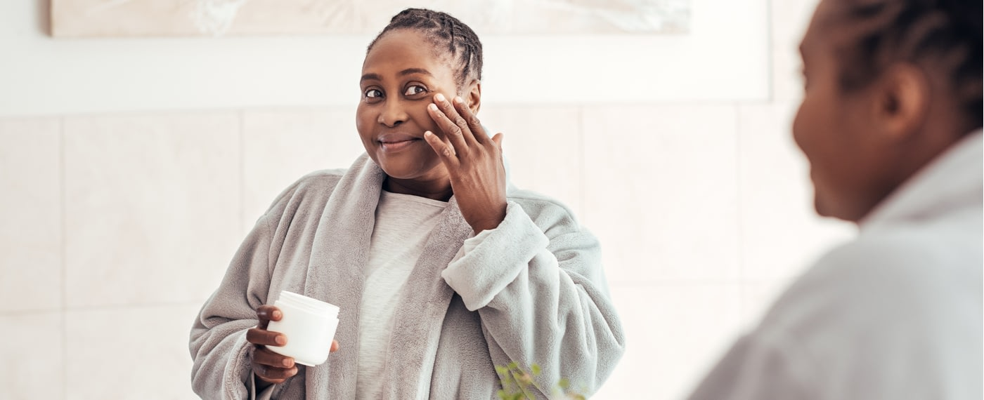 African American woman applying facial product