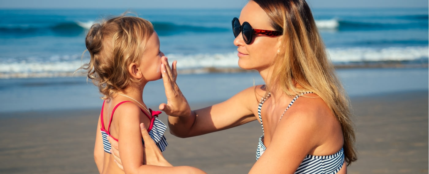 Mother applying sunscreen to small child at the beach