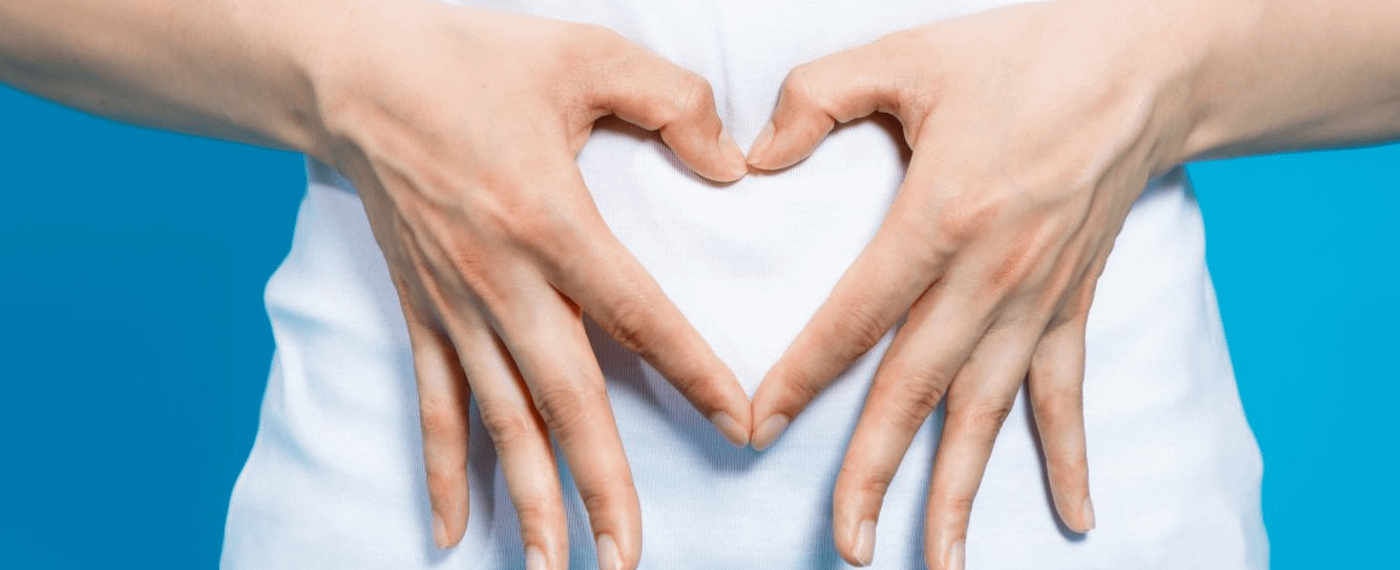 Hands forming the shape of a heart over stomach area