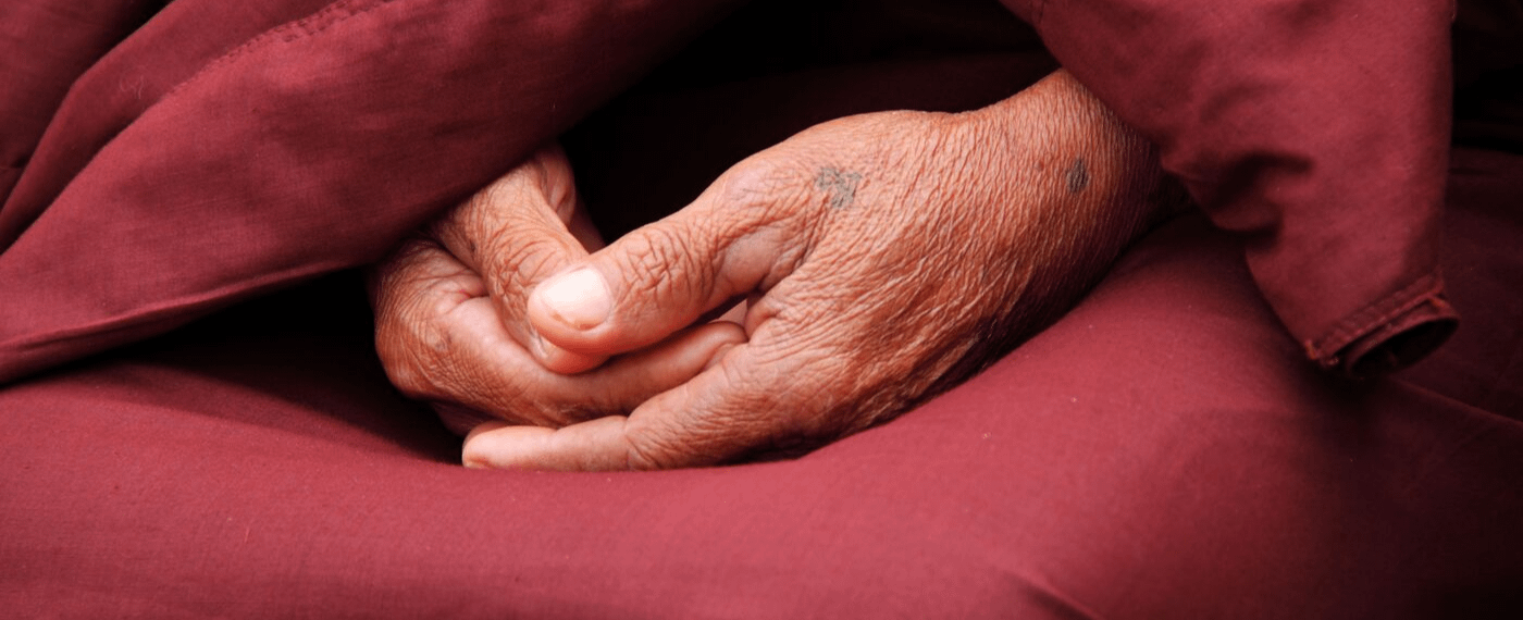 Close up of hands folded neatly in a person's lap