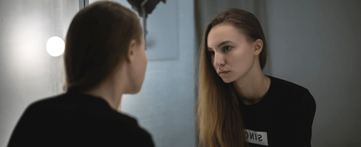 Young woman staring at herself in the mirror