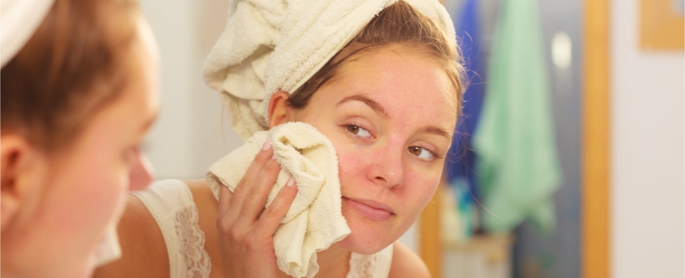 Woman wiping her face with washcloth in the mirror