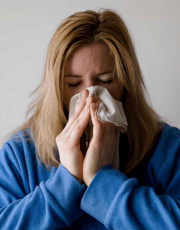 Woman holding a napkin to her nose after sneezing