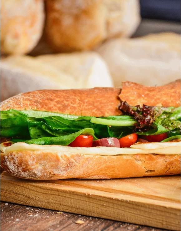 gluten-free pressed sub with cheese, lettuce, and tomatoes