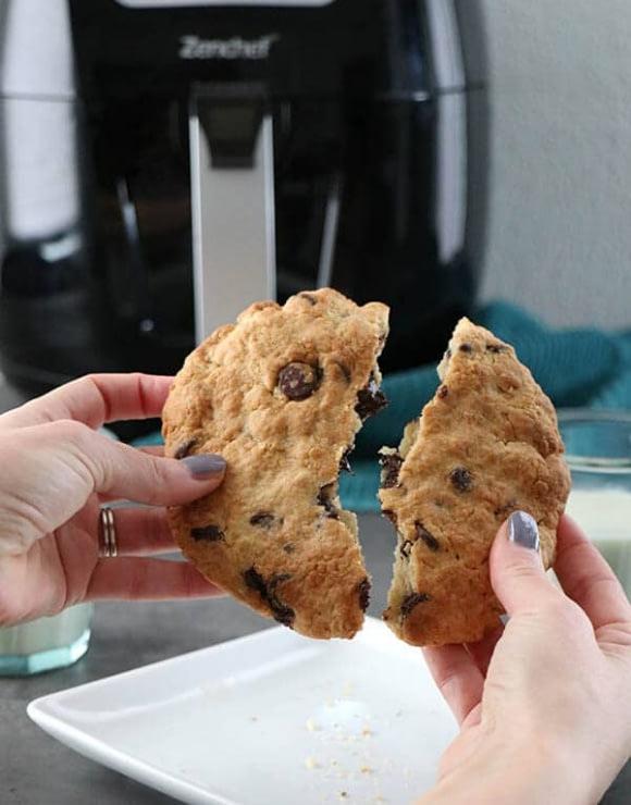 A large air fried vegan chocolate chip cookie being broken in half
