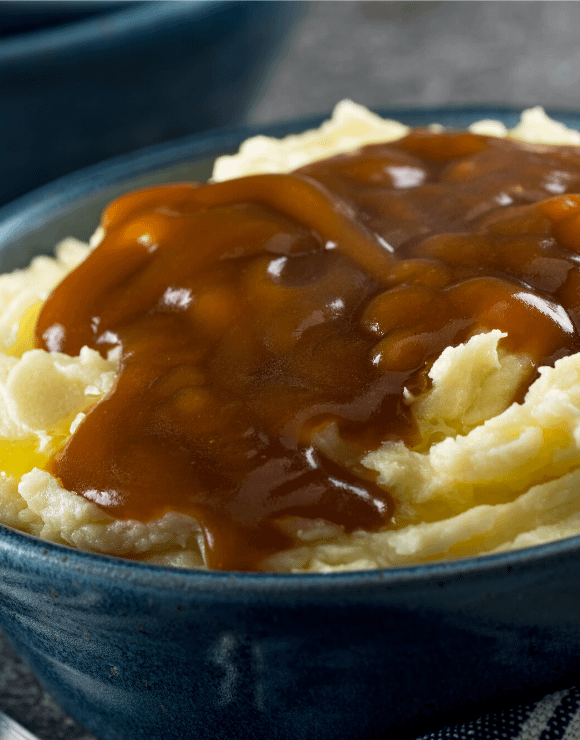 Vegan gravy flowing through swirls of mashed cauliflower
