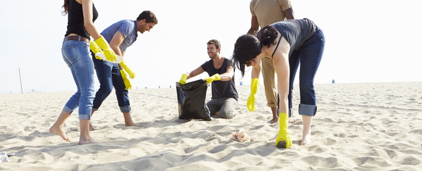 a group of friends picking up plastic on the beach