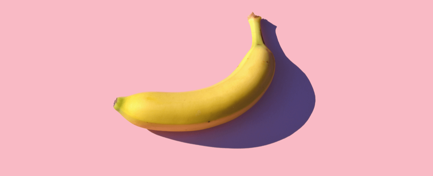a yellow banana against a pink background