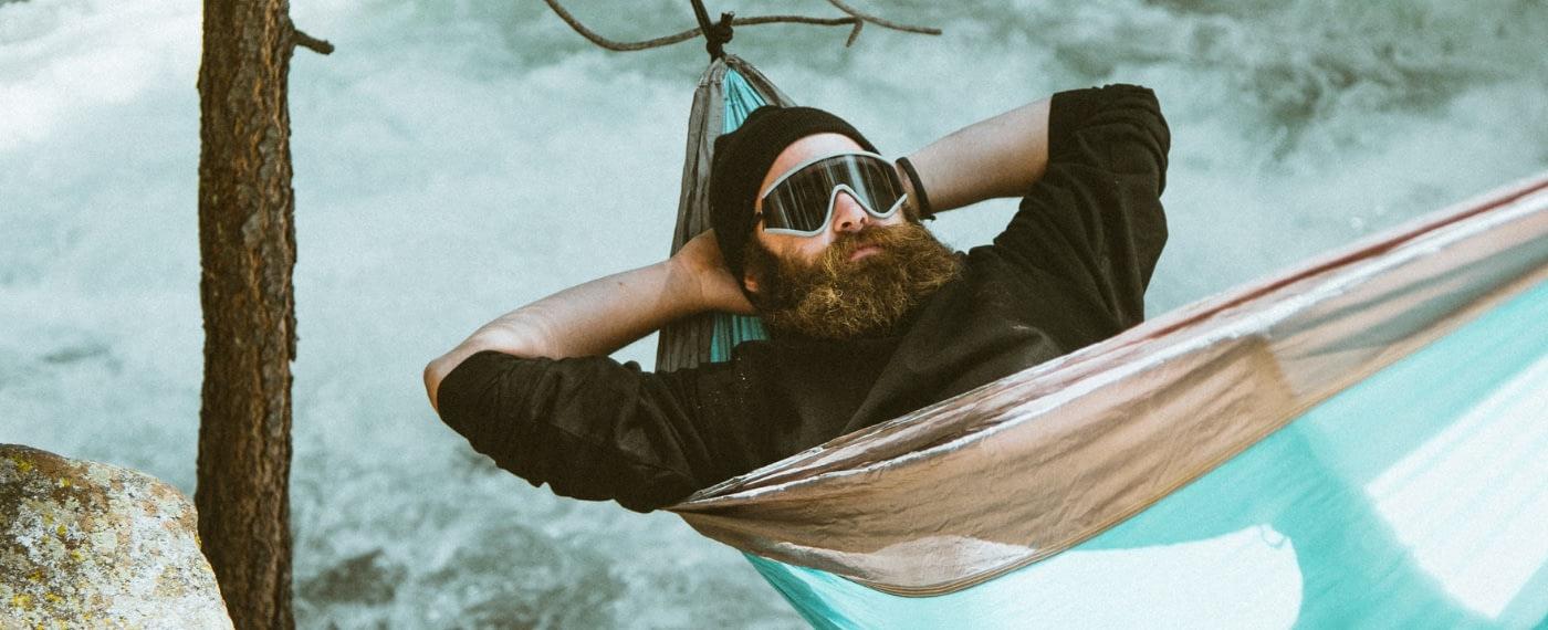 Bearded man relaxing in a hammock in snowy forest