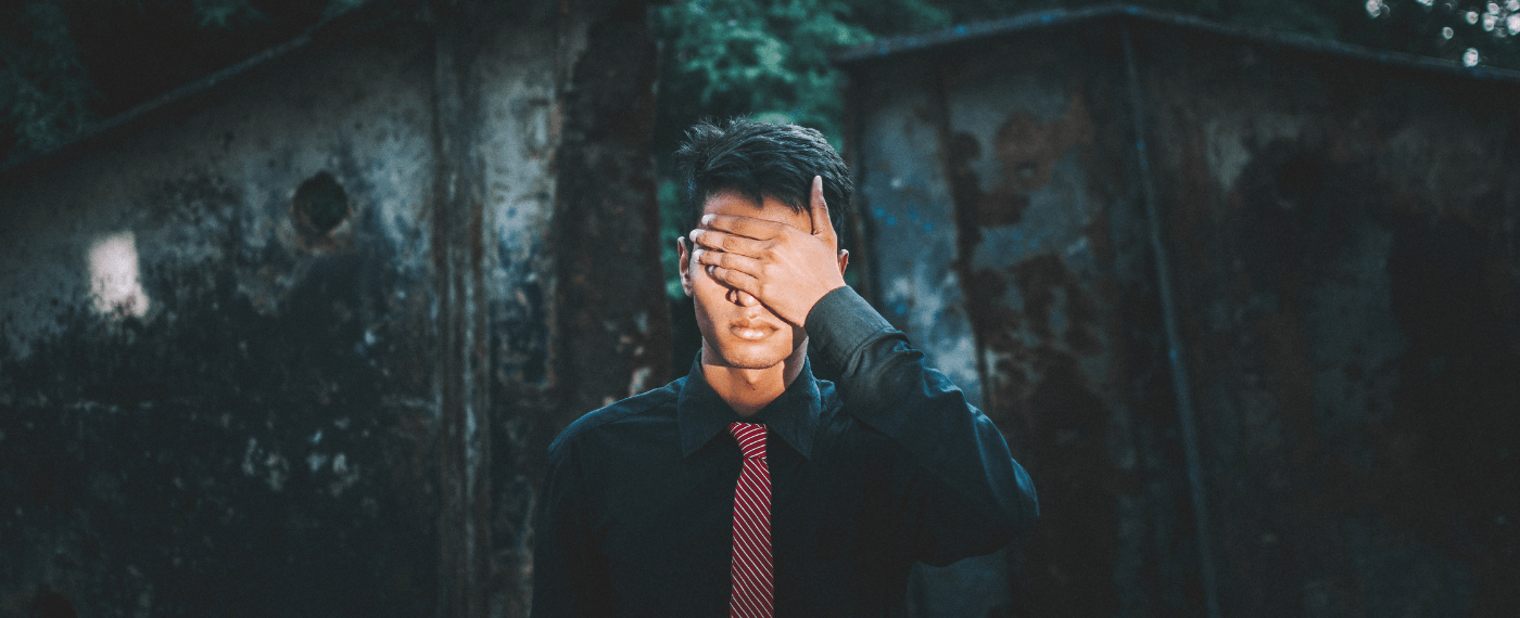 A man covers his face in shame realizing his self-care is selfish