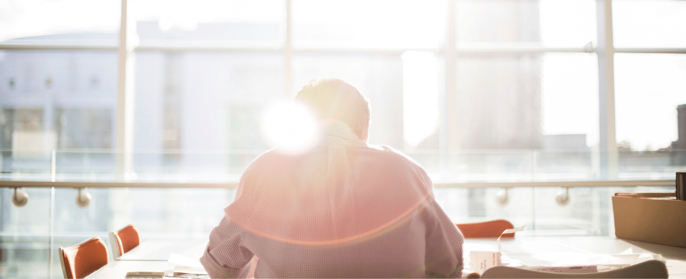 Man sitting in front of windows taking in sunlight to aid with mental health