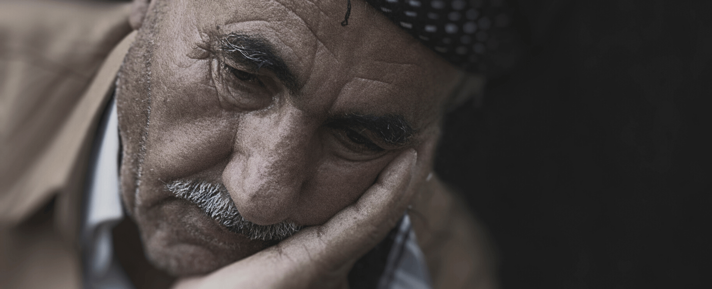 Stressed out older male resting his head against his hand