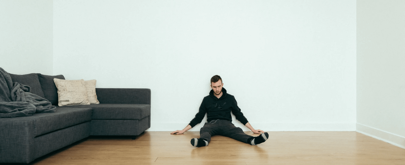 Stresed out man sits on the floor of living room against a wall