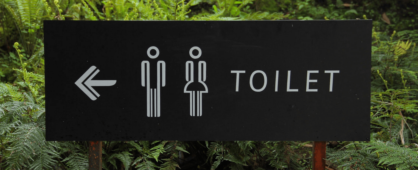 Sign pointing to restrooms due to a bad gut while traveling