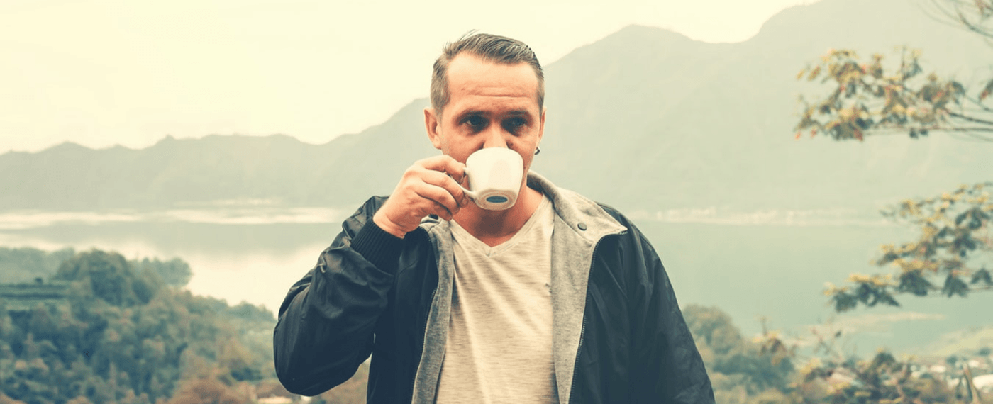 Man drinking a cup of coffee outdoors to help with breathing