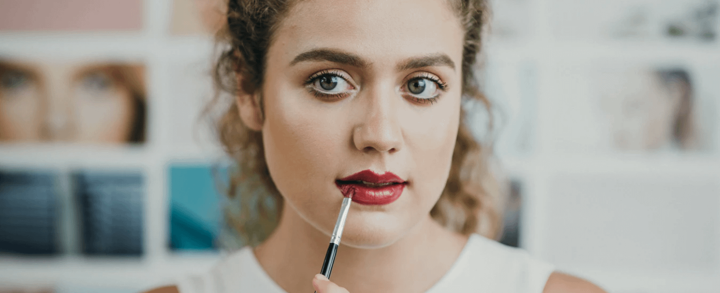 Woman applying beauty product to her lips