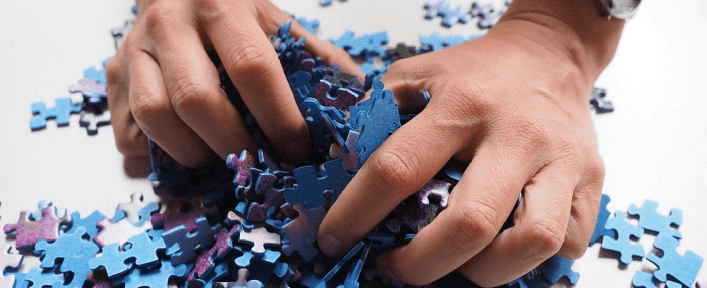 Puzzle pieces being bunched up together in hands