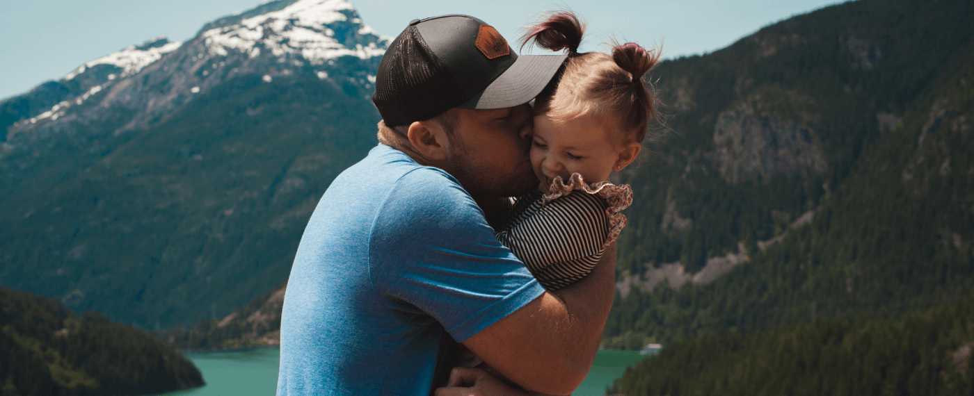 Single father kissing her young daughter in front of a mountain