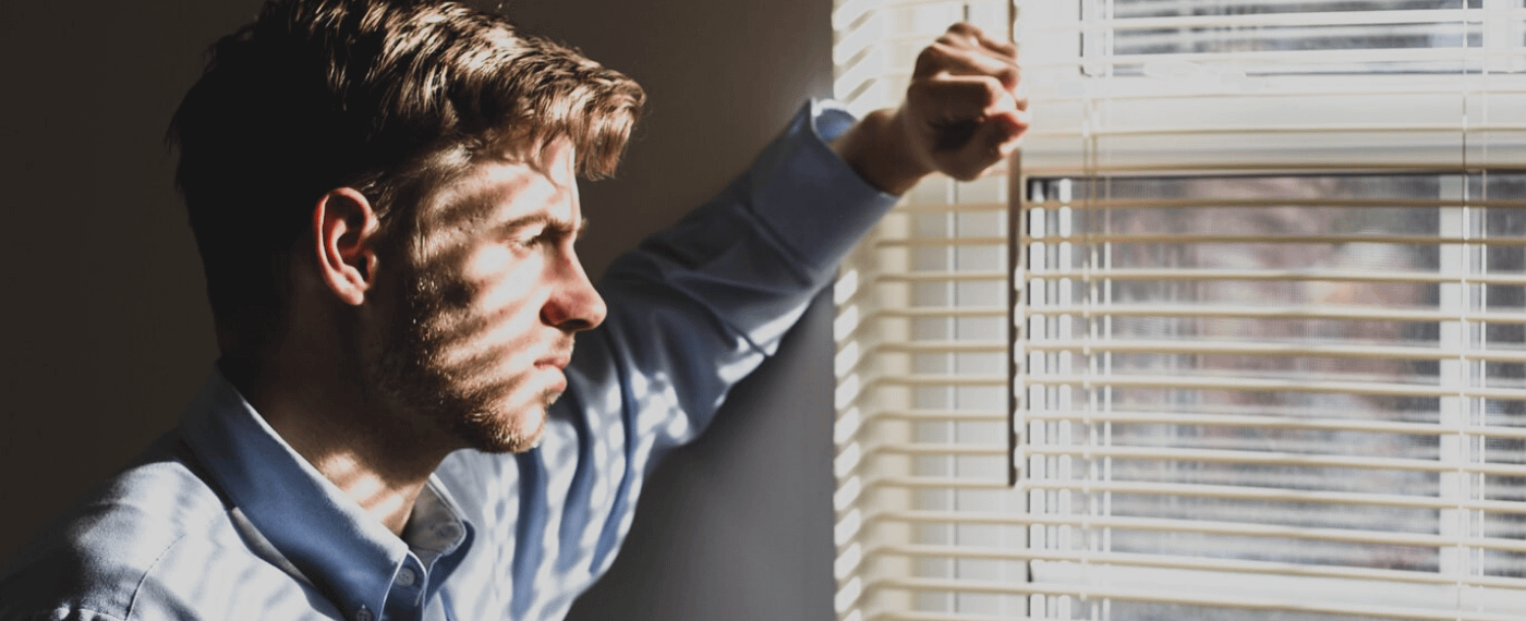 Man looking through blinds of a window with sunlight pouring thorugh