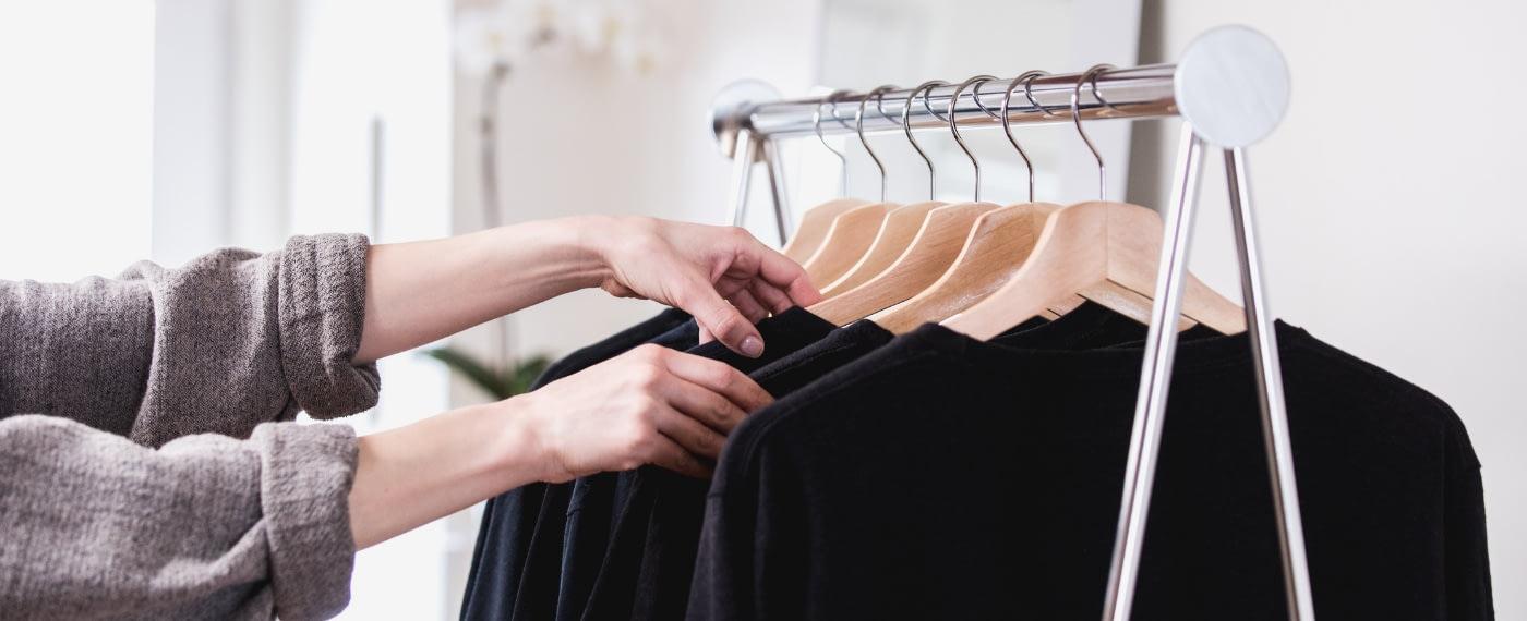 woman detoxing her closet of multiple black shirts